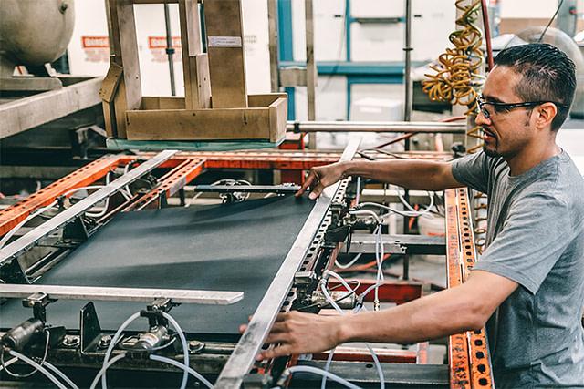 Tempe, AZ employee usingThick gauge thermoforming machine loading sheet into machine